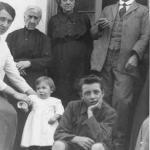 Mario, a un anno e mezzo, con la vestina bianca, tra la mamma e il fratello Toni, dietro i nonni.
